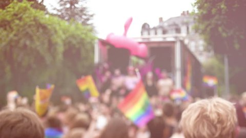 STRASBOURG, FRANCE - CIRCA 2018: Cinematic flare over large crowd of people dancing under house trance electronic music near gay truck with gay and lesbians queers at annual FestiGays pride