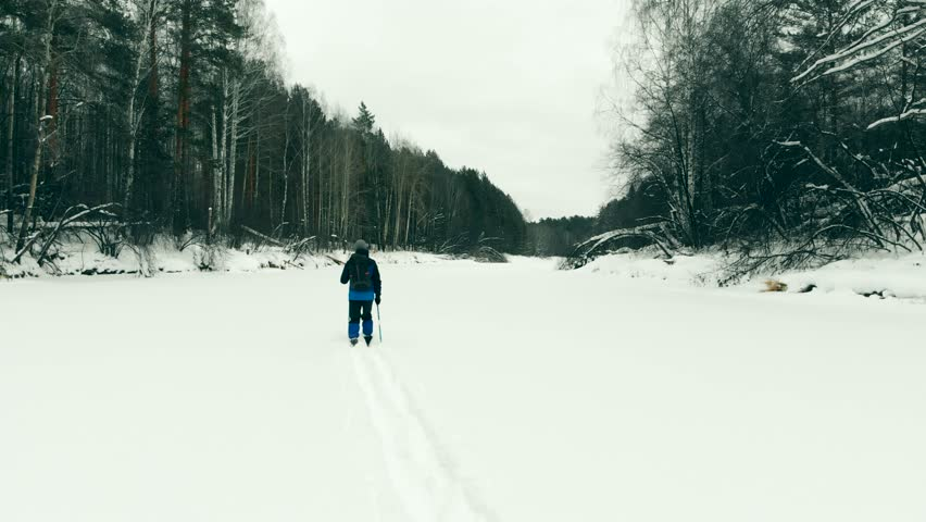 Aerial view of a person cross country skiing. Winter Sports: A Skier Skiing Cross Country Trail. Winter Sports Active Lifestyle. Young Man Skier Skiing Countryside. Skiing Cross Country Winter Snow