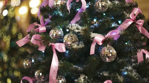 Gimbal tilt up shot of artificial christmas green tree with artificial snow decorated with silver balls, pink ribbons and long white garland