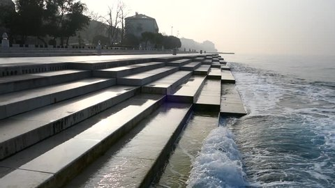 Zadar Croatia February 21st 2019 sea organ with wave on the stairs and fog above city in the sunrise