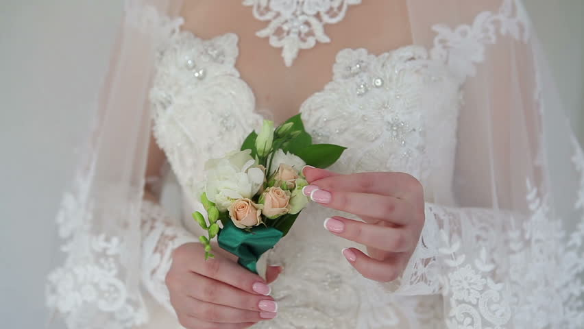 Bride. The girl in a white wedding dress holds in her hands a flower boutonniere.  #1025583092