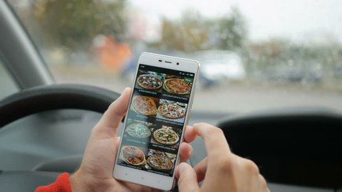 Driver using his smartphone to order pizza online. Man Orders Pizza Using Online Delivery Service With Smartphone. Person sitting in the car and orders using Pizza mobile app
