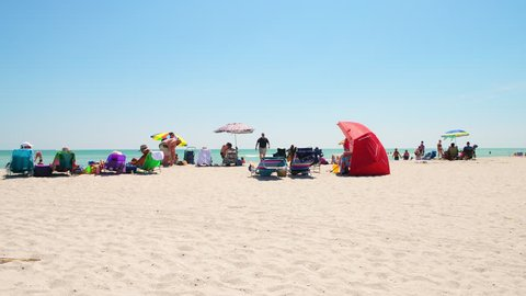 Sanibel Island, USA - April 29, 2018: Bowman's beach with people on sand crowd crowded coast and chairs during sunny day