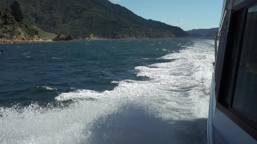 Foamy waves breaking on side of cruise boat in Marlborough Sounds, New Zealand with green hills in background | Shutterstock HD Video #1025640932