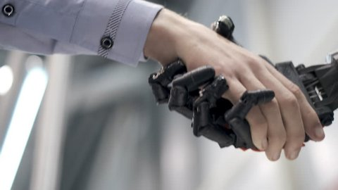 Future is now. Male hand of young student scientist inventor shakes robotic arm. Hand of a man shaking hands with robot. Robotic and human hands join in a handshake.