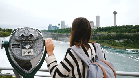 Camera slides behind happy tourist woman with one hand on coin operated binoculars at epic Niagara waterfall slow motion