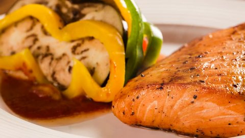 Slide shot Salmon fillet with mixed vegetables. Smoke.
