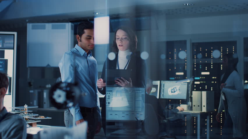 In Technology Research Facility: Female Project Manager Talks With Chief Engineer, they Consult Tablet Computer. Team of Industrial Engineers, Developers Work on Engine Design Using Computers. 8K RED | Shutterstock HD Video #1025738132