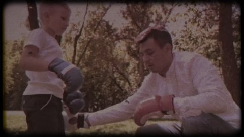 Family video archive. Retro camera 8 mm. Old film. Father and son in boxing gloves play boxing on the lawn near the house. happy childhood.