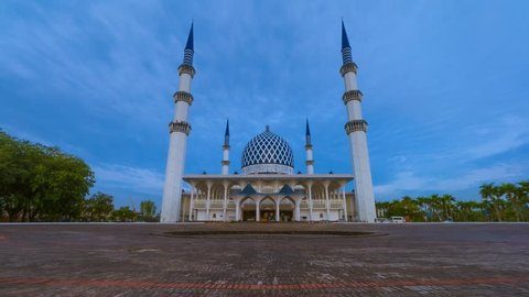 Low Angle Dramatic Sunrise Time Lapse with moonset at a mosque. Shah Alam, Malaysia. Night to day. Slide down and zoom in motion timelapse.