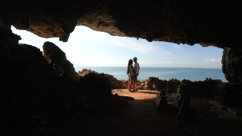Traveler couple people enjoy amazing aerial view from cave on top of mountain on tropical beach. Summer vacation, Travel and Active LifeStyle concept in 4k