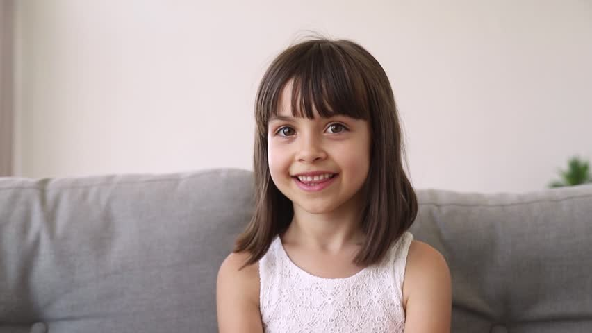 Funny little girl vlogger blogger looking at camera talking recording vlog, cute preschool pretty kid speaking to webcam making online video call having fun waving hand blowing kisses