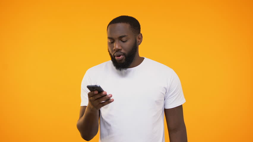 African american guy surprised, saying wow, looking at phone screen, lottery win | Shutterstock HD Video #1025781242