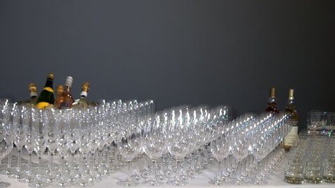 Many glass goblets shine on banquet table on background of gray wall. Elegantly lined up row of wine glasses with bottles of alcohol stand on white tablecloth.