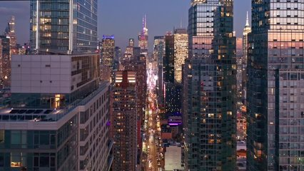 Aerial drone footage of New York skyline along 42nd street canyon, at dusk, with pull back camera motion