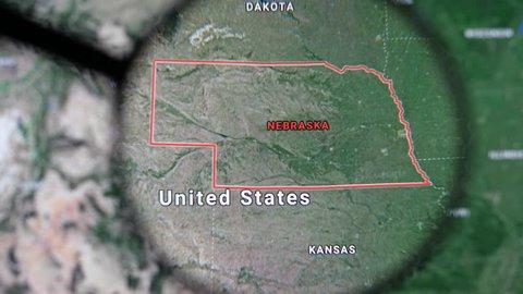MIAMI BEACH. FLORIDA. USA - MARCH 2019: USA, Nebraska on the political map. The borders of Nebraska. Nebraska State under a magnifying glass. Geography of Nebraska in the USA