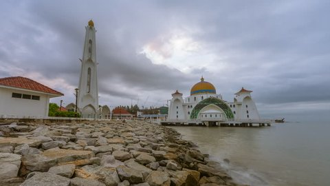 Dramatic Stormy Time lapse of sunrise and fast clouds at a mosque in Melaka, Malaysia at night to day.