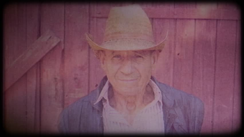 Old farmer in a straw hat near the farm. Portrait of an elderly man. Retiree. Video archive. Retro. Vintage. Farm animals. Raising animals for meat. Agriculture. Organic food. Ranch | Shutterstock HD Video #1025821772