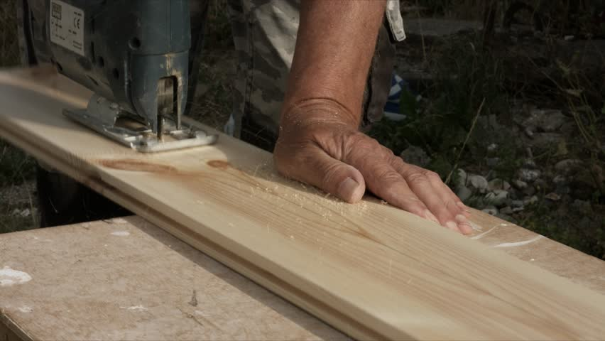 An old man cutting wooden floor with an electric saw. Carpenter working. | Shutterstock HD Video #1025839202