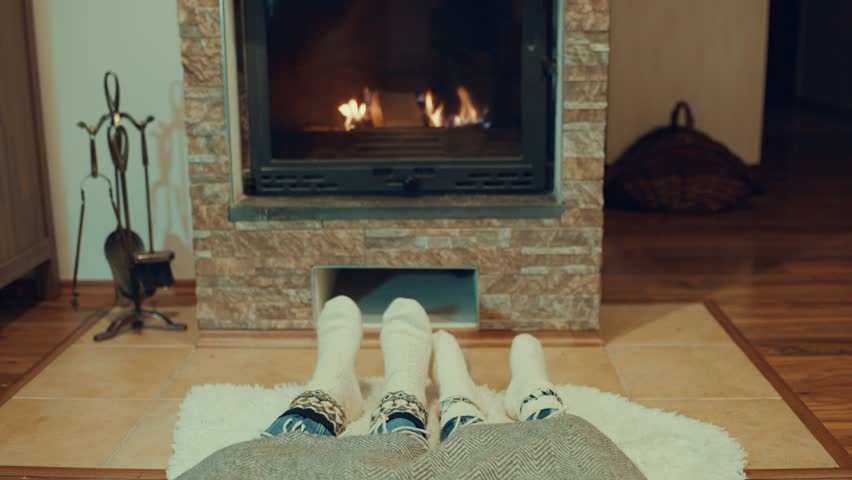 Couple resting by fireplace, Cheerful mother and child at home in knitted socks, near the fire, winter, christmas time | Shutterstock HD Video #1025842082
