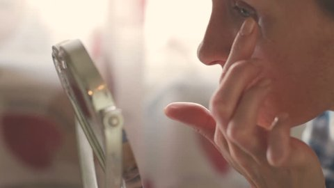 Skin care concept. Woman middle age apply cream on face in front of mirror, close-up