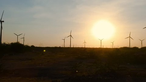 Evening silhouette of windmills with sun setting in background on a cloudy blue sky in Jaisalmer, Jodhpur, Dwarka Gujarat. These clean energy generating wind farms are densely populated in the state