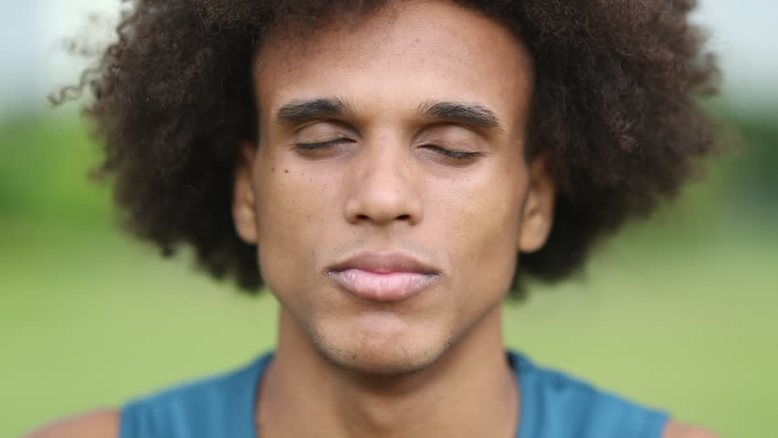Young african man closing eyes taking a deep breath and opening eyes smiling feeling happy | Shutterstock HD Video #1025872232