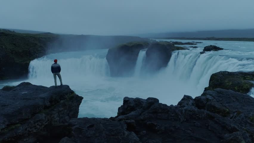 Drone camera flies around hipster young man in blue knit wool sweater and red beanie, stand on edge of cliff or rock overlooking epic mountain icelandic waterfall on moody summer night light | Shutterstock HD Video #1025887952