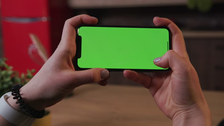 Tokio, Japan - April 7, 2018: Close up woman hand hold use smartphone with horizontal green screen on kitchen at home breakfast browse food girl house shopping play internet abstract slow motion | Shutterstock HD Video #1025899412