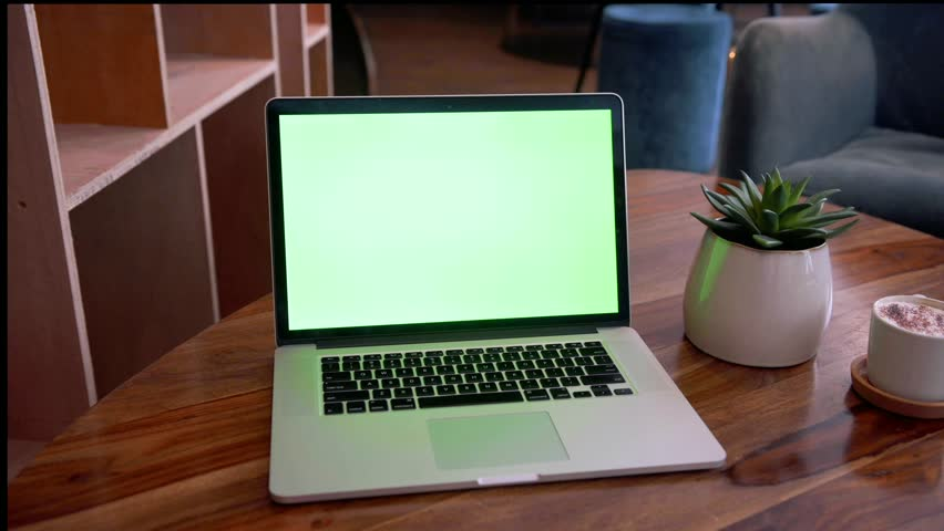 Laptop with green screen on a fancy wooden coffee table  | Shutterstock HD Video #1025900012
