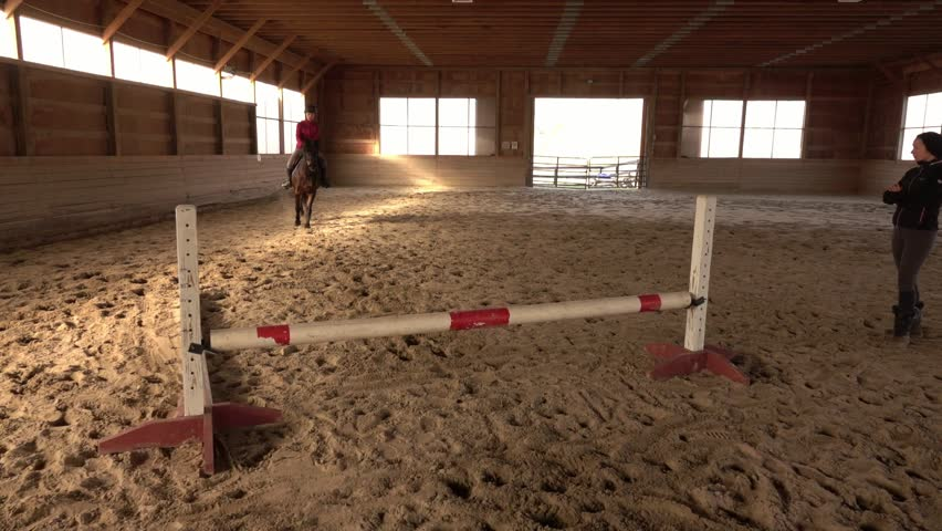 Horse instructor helping learn to jump. Learning and training in the riding school. | Shutterstock HD Video #1025938862