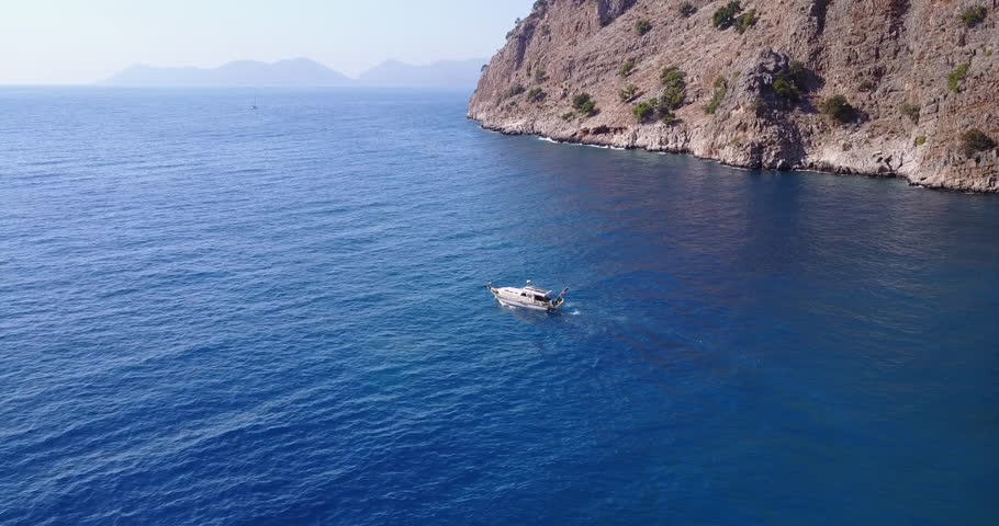 Drone camera following small cruising motor boat at the blue bay | Shutterstock HD Video #1025943002
