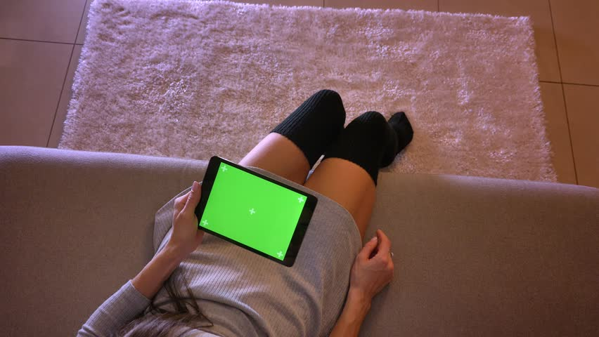 Closeup shoot of young female teenager playing video on the tablet with green screen vertically. Girls legs in cute socks sitting on the sofa indoors | Shutterstock HD Video #1025959502