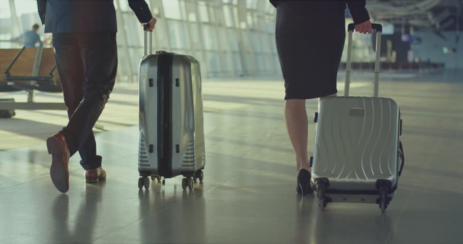 Back view on the Caucasian business people walking the airport and carrying their suitcases with wheels while travelling to the working trip. Rear. | Shutterstock HD Video #1026000572