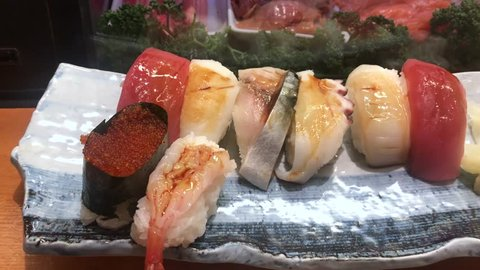 Various of Sushi and Sashimi.Japanese national dishes seafood are most of the ingredients come from the sea,Assort Japanese rice, shrimps, fish, scallops, salmon, tuna, squid, ginger on plate.