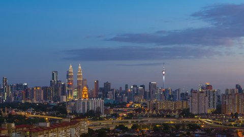 Time lapse: Kuala Lumpur city view during dusk overlooking the city skyline at sunset from day to night in Malaysia.
