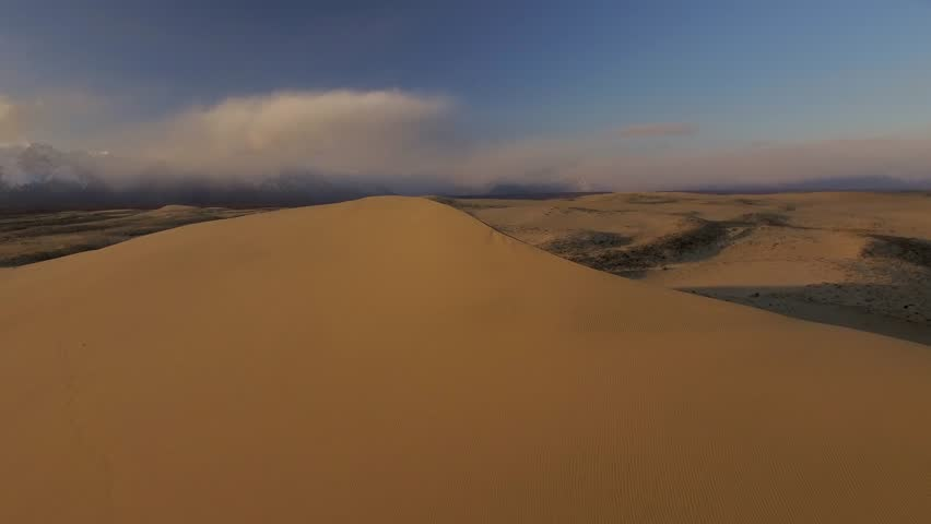 Unique Desert Sands Chara Yellow top dunes Siberia tundra picturesque landscape. Trans-Baikal Russia. Udokan mountains. Natural monument. Sunset Winter blue sky clouds. Aerial Low drift  horizon #1026079742