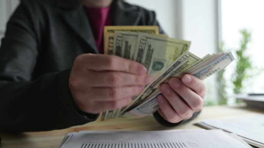 Businesswoman counting dollars in the office, handheld footage with selective focus #1026132242