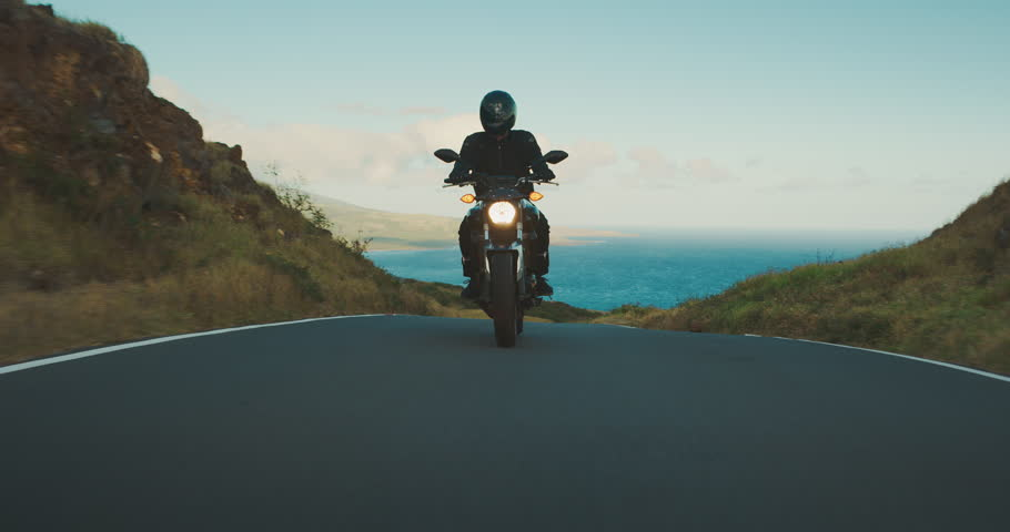 Motorcyclist riding fast on country road with ocean in the background, motorcycle adventure lifestyle