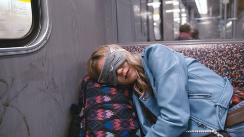 Slow Motion Young beautiful girl in the Blindfold on the eyes, fell asleep on the subway train. Head put on a backpack.