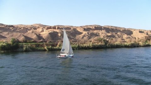 Traditional White Felucca Sail Boat on the River Nile with an Arid Desert Landscape as a Background