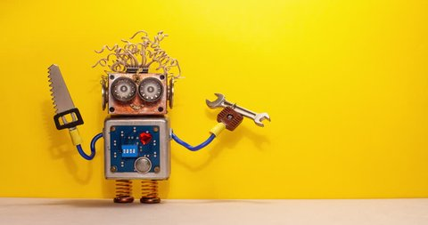 Funny robot handyman technician rotates saw and hand wrench. Fixing maintenance concept. Creative design robotic toy character. Yellow wall floor background. Copy space.