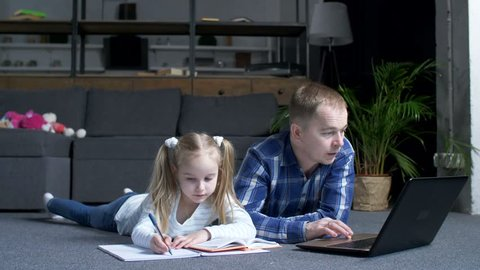 Advanced father with laptop searching online explanations to educational material for little daughter during home schooling. Caring father with preadolescent girl studying online course using latop pc