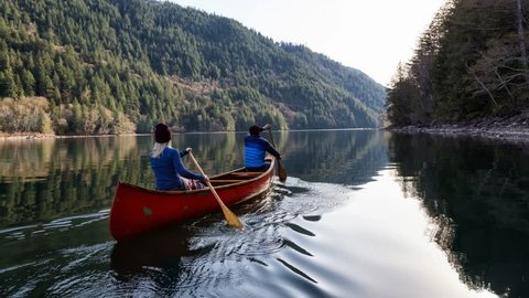 Couple friends canoeing on a wooden canoe during a sunny day. Taken in Harrison River, East of Vancouver, British Columbia, Canada. Still Image Continuous Animation