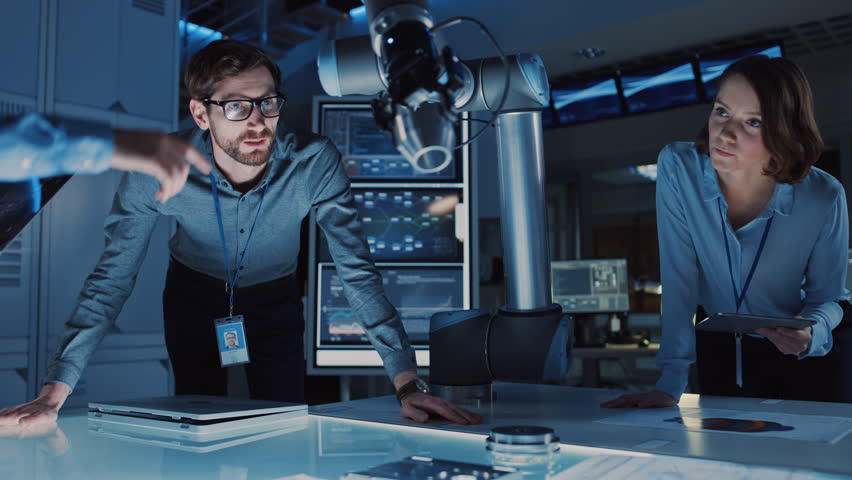 Diverse Team of Engineers with Laptop and a Tablet Analyse and Discuss How a Futuristic Robotic Arm Works and Moves a Metal Object. They are in a High Tech Research Laboratory with Modern Equipment. | Shutterstock HD Video #1026241952