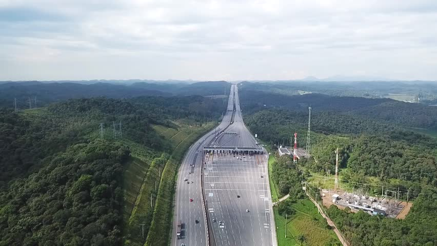 Drone aerial shot from a highway next a river dam in Sao Paulo showing cars - trucks and traffic and a toll
