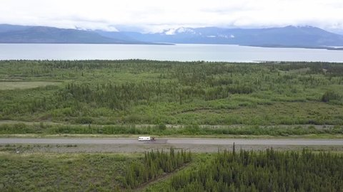 Aerial side view of a RV motorhome driving along the Alaska Highway in Yukon, Canada, with a lake in the background.