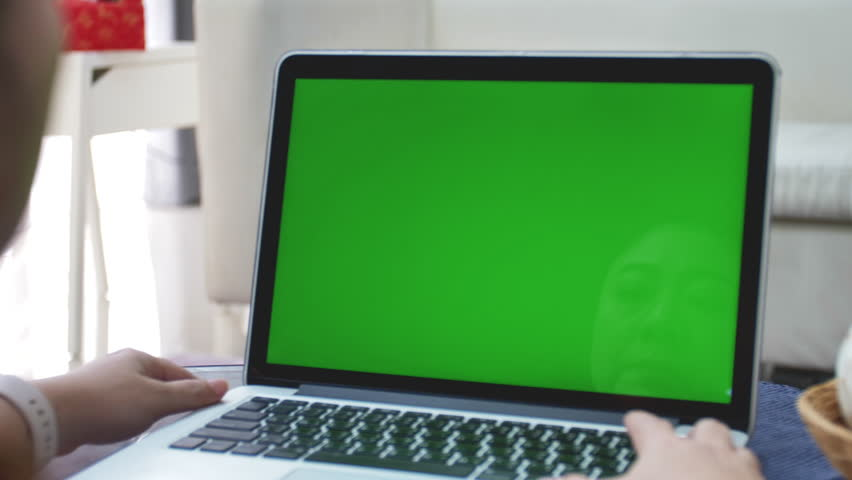 Over the shoulder shot of Asian woman looking at green screen. Office person using laptop computer with laptop green screen, 4K dolly shot #1026299972
