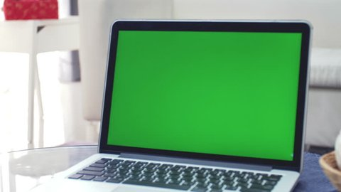 Laptop Computer Showing Green Chroma Key Screen Stands on a Desk in the Living Room. In the Background Cozy Living Room. Dolly Zoom out Shot. 4K