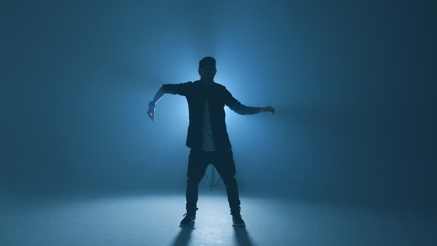 Full length portrait of a young man dancer in casual street wear dancing funky hip hop on isolated studio neon blue background | Shutterstock HD Video #1026306992